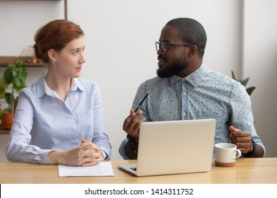 Black african company member training candidate, sharing thoughts explaining idea with female coworker. Two diverse businesspeople sitting together in office. Coaching or brainstorming session concept
