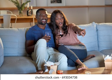 Black african couple watching movie television together having date night