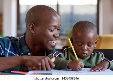 Black african family together at home, dad watching kid child boy son drawing pictures