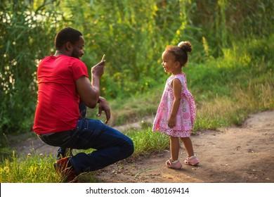Der schwarze afrikanische Vater fotografiert seine Tochter mit Mobiltelefonen.