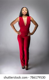 Black African female fashion model wearing red pantsuit for spring design.  The clothing looks semi formal or casual but elegant.  The image depits modern style trend.