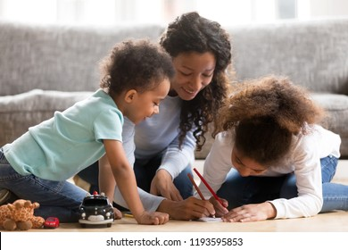 Black African loving mother help to their children draw. Positive mom sitting with toddler son and preschool daughter on a wooden warm floor spend free time on weekend together in living room at home
