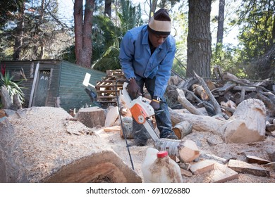 Black african male in south africa carves a sculpture from a piece of pine using a chainsaw