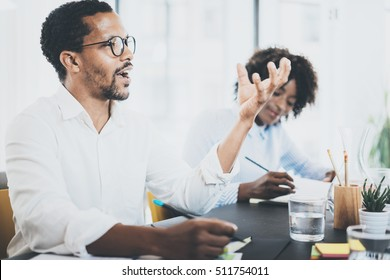 Black african man explaning business idea in meeting room.Two young coworking people working together in a modern office.Horizontal,blurred background