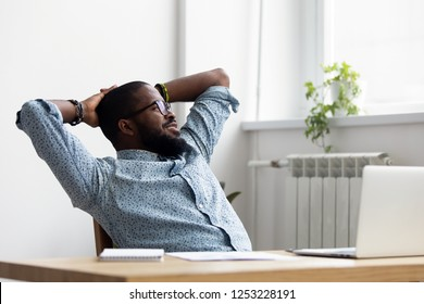 Black african millennial businessman take break during workday relaxing sitting on chair at office desk hold hands behind head looking at window thinking feels good. Stress relief daydreaming concept