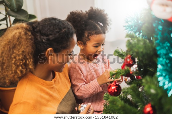 Black african mother and her cute daughter decorating christmas tree for christmas and happy new concept