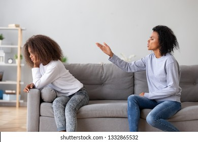 Black african mother scolding teen daughter people sitting on sofa at home. Older and younger sisters conflict, teen problems, misunderstanding of different generations, parent child relations concept