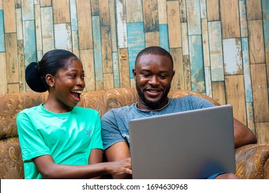 black African Nigeria couple smiling from funny content on website. young woman shopping online with boyfriend