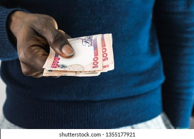 Black African Nigerian man holding Nigerian Naira money in hand. Buinessman paying for or giving money to seller for business transfer and payment concept