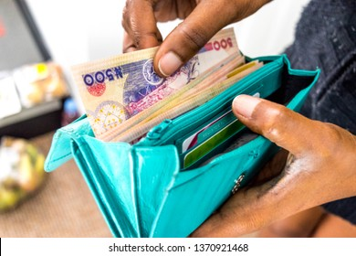 Black African Nigerian woman holding Nigerian Naira money in hand from Nigeria Naira. Buiness woman paying for or giving money to seller for business from leather wallet transfer and payment concept
