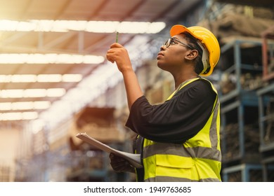 Black African professional women worker working count checking inventory production stock control in business factory  industry warehouse waring engineer suit and helmet for safety