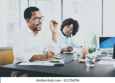 Black african project manager explaning business task in meeting room.Two young entrepreneurs working together in a modern office.Horizontal,blurred background