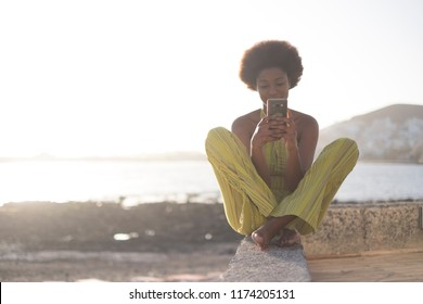black african race young beautiful model girl 25 years old use the phone and check internet social media sitting ona wall near the ocean and water with bright sunset in background. happy people