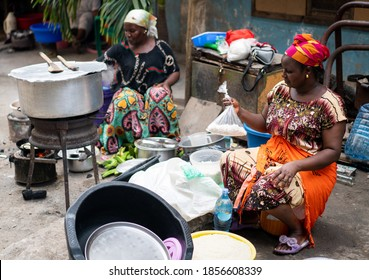 Black African woman cooking and selling street food