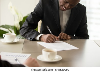 Black afro american young businessman wearing suit puts signature official document during meeting with partner, satisfied client signing contract agreement concept, making profitable deal, close up