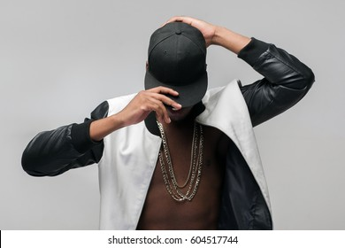 Black afroamerican rebellious rapper on grey background. Closed face, rejection, separated, reluctance to see, breaking off. Ghetto, challenge to society, cheeky, cool