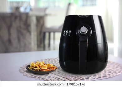 a black air fryer or oil free fryer appliance is on grey table in the dining room with deep fried banana chips in small black dish ( clipping path included )