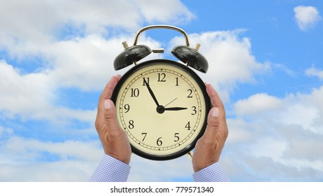 Black alarm clock with 2:55 time held in hands blue sky clouds background