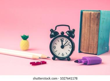 black alarm clock, book, markers, pencil