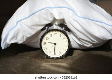 Black alarm clock covered by a white pillow
