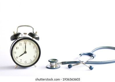 Black alarm clock and doctor stethoscope on natural daylight white background