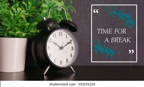 Black alarm clock and green plant with word Time For A Break.Time concept