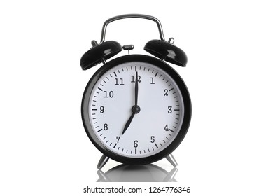 Black alarm clock isolated on white background shows seven o clock in the morning time to get up to wake up and have breakfast morning or evening run to go to work 7 am pm.
