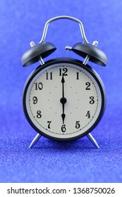 Black Alarm clock isolated on blue background