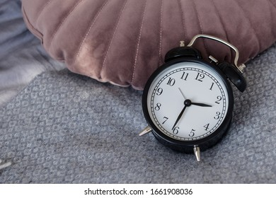 Black alarm clock in a made-up bed on a gray textured bedspread, against a pink and blue velor pillow. Early rise. Space for text.