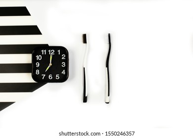 Black alarm clock with manual toothbrush set on white and black background. Toothbrushes in two colours. Dental health, teeth whitening concept. top view, concept of dental care.