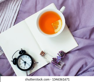 Black alarm clock in morning light, cup of tea with lemon, flowers of lilac and notebook on lilac background. Flat lay