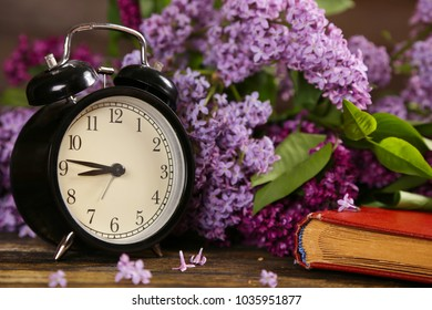 Black alarm clock, an old book and lilac flowers as a background. Spring time change. Good Morning Hello Spring concept