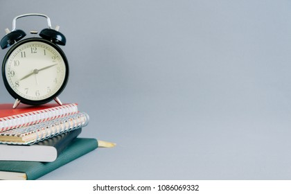 Black alarm clock on book,Education concept with copy space background.