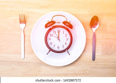 Black Alarm Clock on Fork Ceramic Dish and Stainless Steel Spoon on a Wooden Table in sunset background, Food Timing Cycles for Eating, Healthy Eat Meal Time and Reminder Concept.