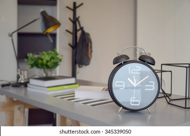 black alarm clock on work table at home