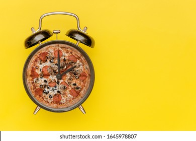 Black alarm clock with a pizza instead of a dial. Yellow background.