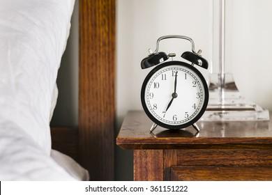 black alarm clock showing 7 o'clock on a bedside table