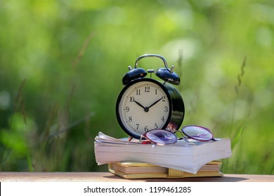 Black alarm clock stacked on organize book with nature bokeh background