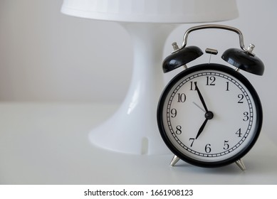 A black alarm clock stands on a white nightstand against a white lamp and white wall. Early rise. Space for text.