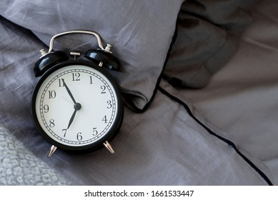 Black alarm clock in unmade bed on crumpled, gray bedding. Early rise. Space for text.