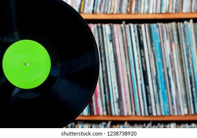 Black album positioned in front of bookcase filled with spines of covers  you can use for your audio store, selling recordings or uptick in the interest in vinyl