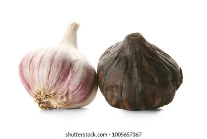 Black (Allium sativum) and white garlic bulbs on white background