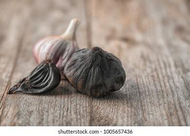 Black (Allium sativum) and white garlic bulbs on wooden table