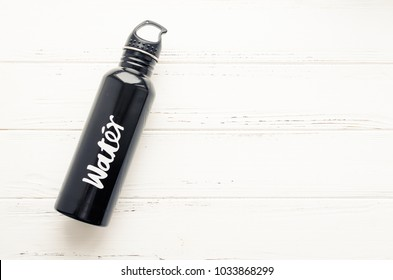 Black aluminum reusable water bottle on white shabby chic wooden background with place for text. Drink more concept. Top view. Copy space.