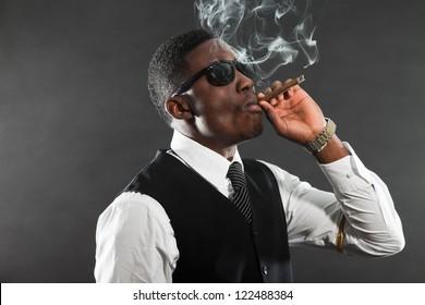 Black american mafia gangster man in suit smoking cigar.