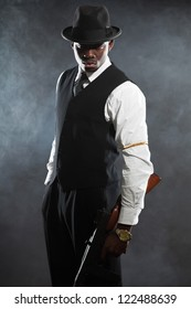 Black american mafia gangster man in suit with gun.