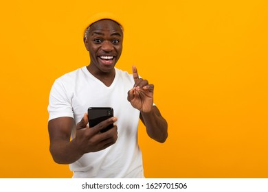 black american man smiling holding a phone in his hands on an orange background - Shutterstock ID 1629701506
