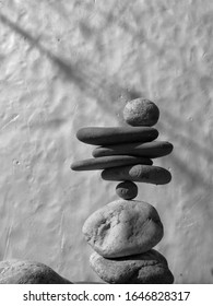 black ana white picture of balanced stones on white background, rock balancing art