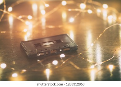 A black analog cassette tape on a wood table with soft lights.