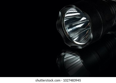 black anodized aluminium waterproof tactical flashlight on black background